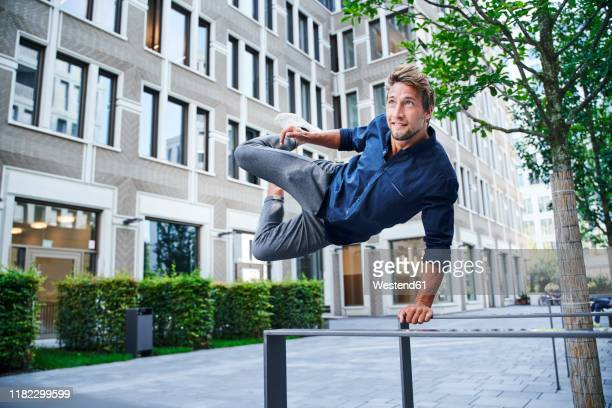 young man jumping over railing in the city - parapetto barriera foto e immagini stock