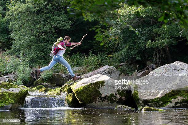 Young man jumping over the river