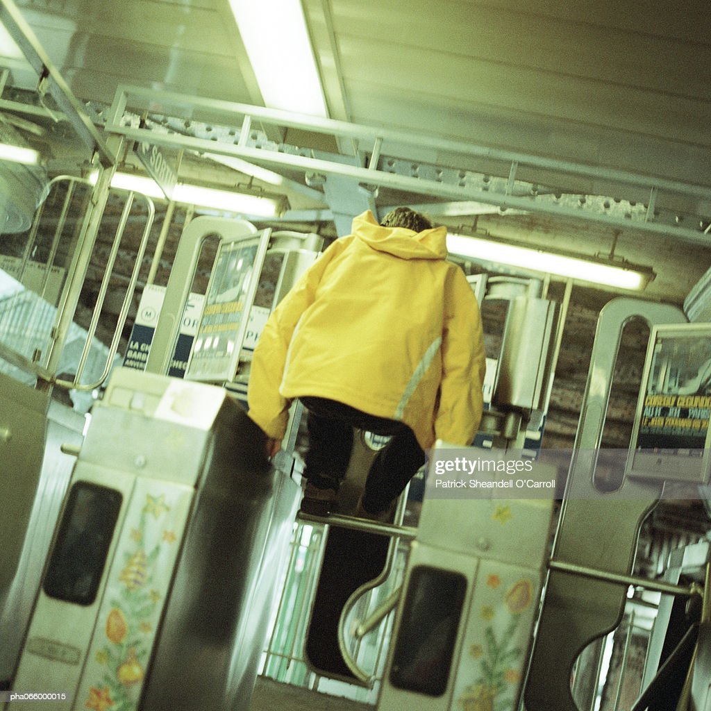 Young man jumping over turnstile in subway : Stock Photo