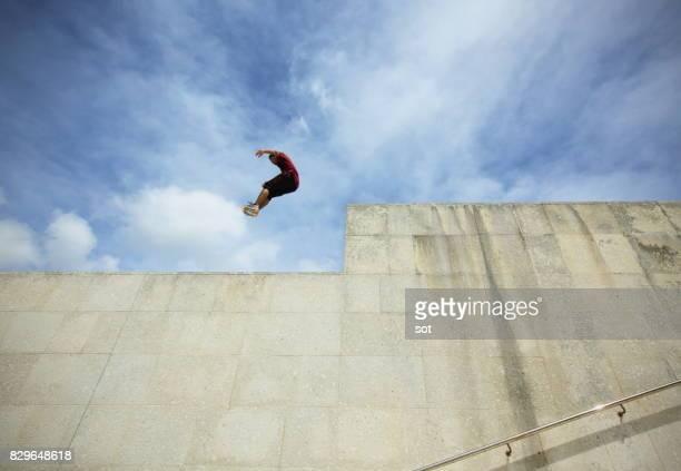 Junger Mann springen Leistung auf Betonwand
