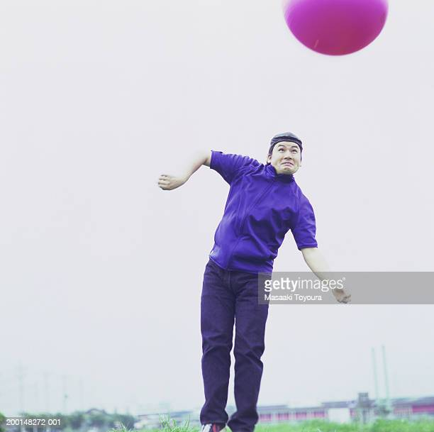 Young man jumping to hit red ball