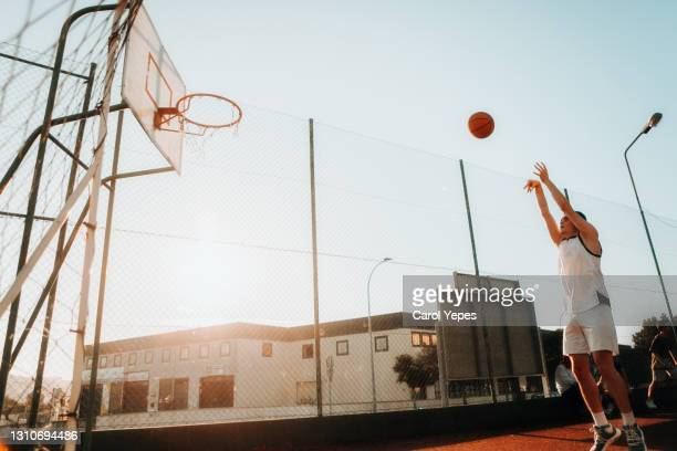 young man jumping to score hoop in basketball - basketball uniform stock pictures, royalty-free photos & images