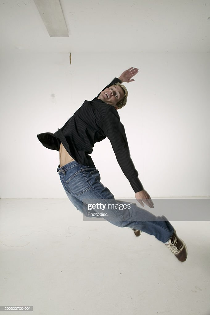 Young man jumping up for joy, portrait : Stock Photo
