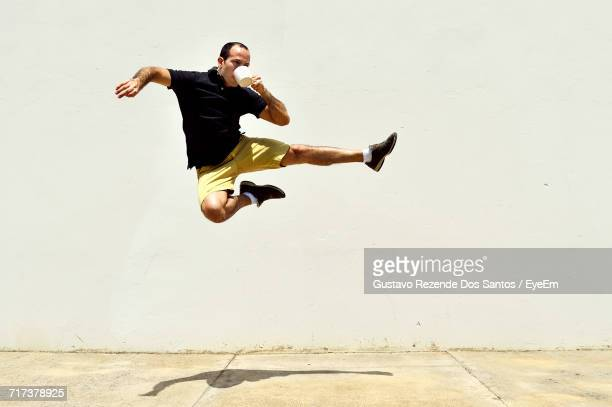 young man jumping while drinking coffee - stunt stock photos and pictures