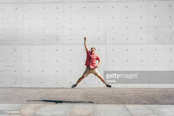 young man jumping with hand raised against gray wall at paul-loebe-haus - legs apart stock pictures, royalty-free photos & images