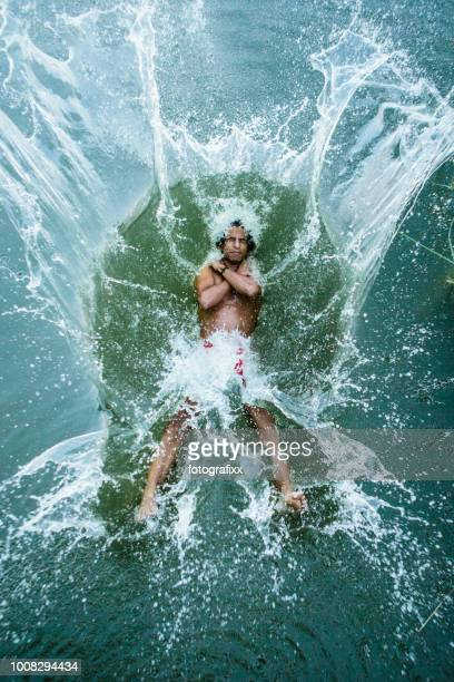 young man jumps backwards into a lake, water splashes around - bending over backwards stock photos and pictures