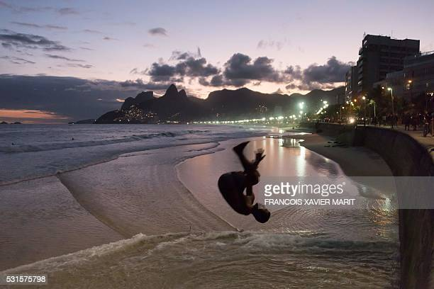 TOPSHOT A young man jumps from a wall on the beach of Arpoador neighbouring the famous Ipanema beach on May 14 2016 as the sun sets in Rio de Janeiro...