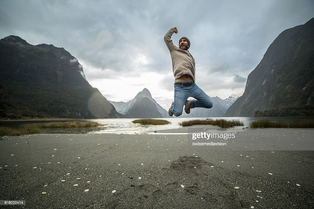 Young man jumps in front of Mitre peak, New Zealand : Photo