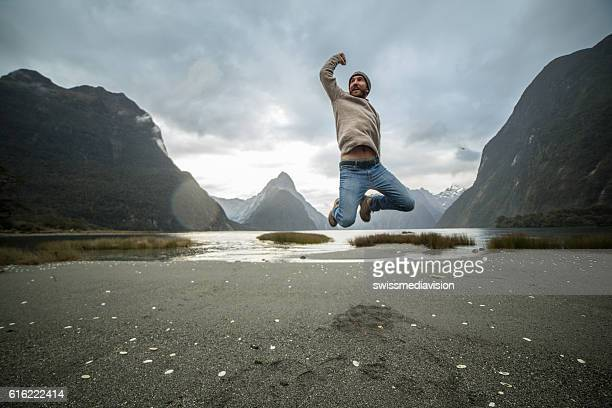 Young man jumps in front of Mitre peak, New Zealand