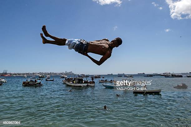 A young man jumps into the sea at Boa Viagem beach in Salvador Bahía Brazil on January 1 2015 AFP PHOTO / YASUYOSHI CHIBA