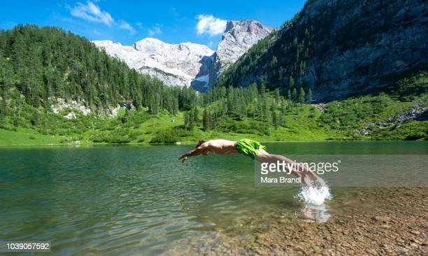Young man jumps into the water, lake Gruensee at the hiking trail to the Kaerlinger Haus, Berchtesgaden National Park, Berchtesgadener Land, Upper Bavaria, Bavaria, Germany