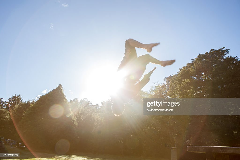 Young man jumps mid-air against blue sky : Stockfoto