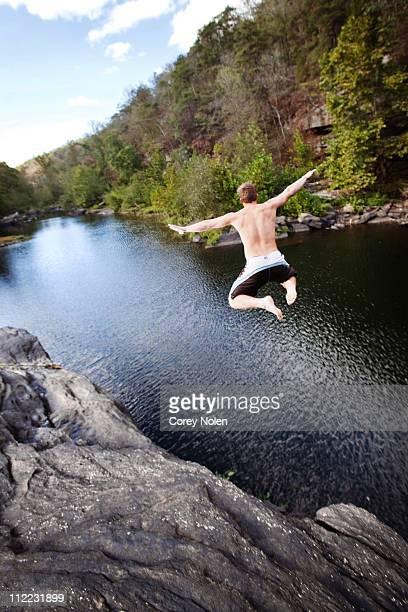 Young man jumps off rock cliffs into a lagoon at High Falls Park, Geraldine, Alabama.