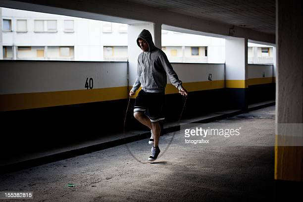 young man jumps rope in empty Parking Garage in Ghetto