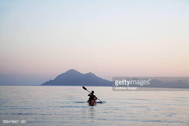 Young man kayaking into ocean
