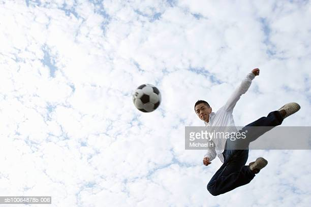 Young man kicking football in air, low angle view