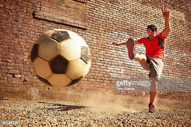 Young man kicking soccer ball on wasteland