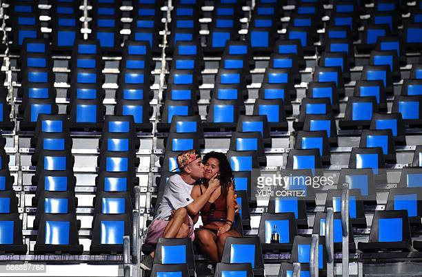 A young man kisses a girl ahead of a boxing match at the Rio 2016 Olympic Games at the Riocentro Pavilion 6 in Rio de Janeiro on August 7 2016 / AFP...