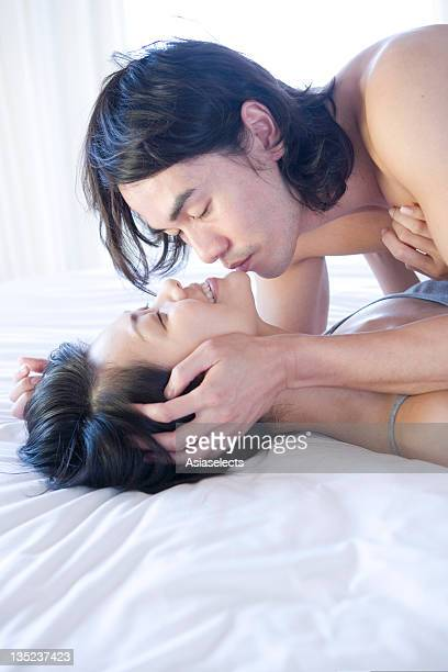 Young man kissing a young woman lying on the bed and smiling, Phuket, Thailand