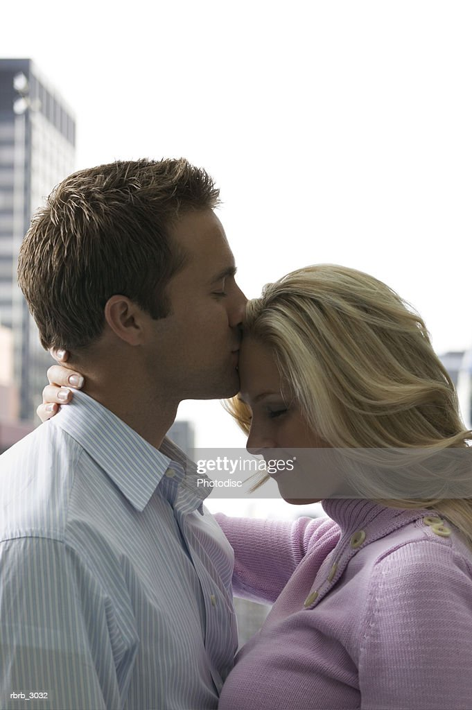 Young man kissing a young woman on the forehead : Foto de stock
