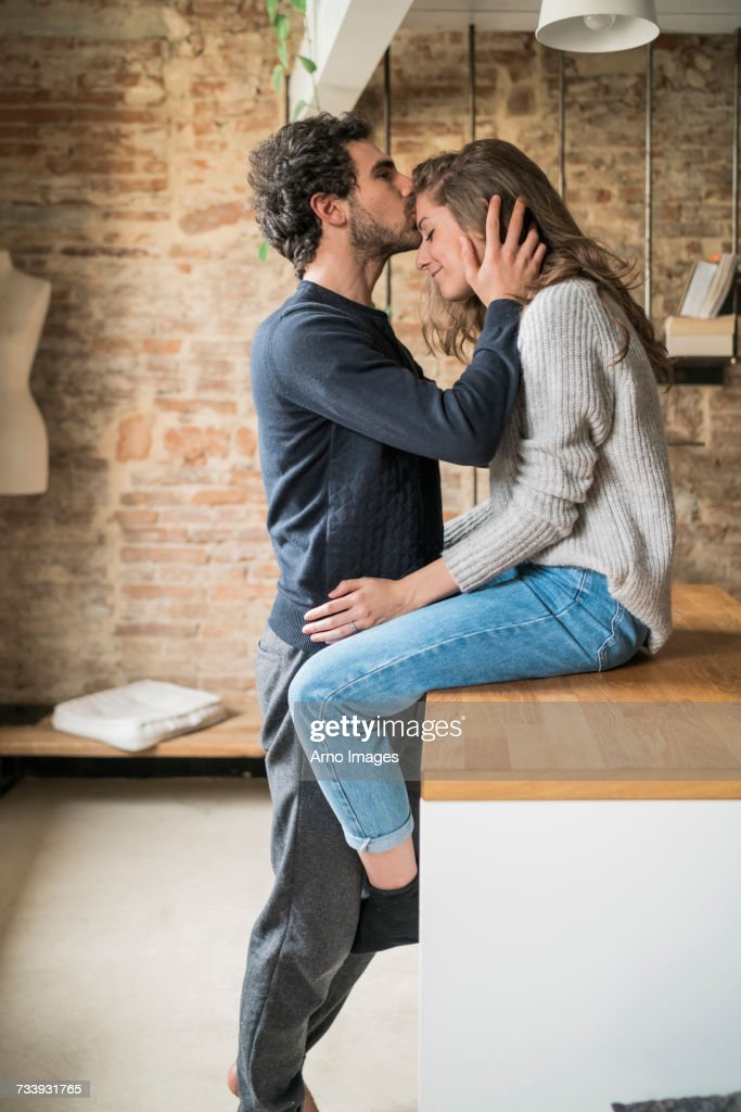 Young man kissing girlfriend on forehead at kitchen bench : Stock Photo