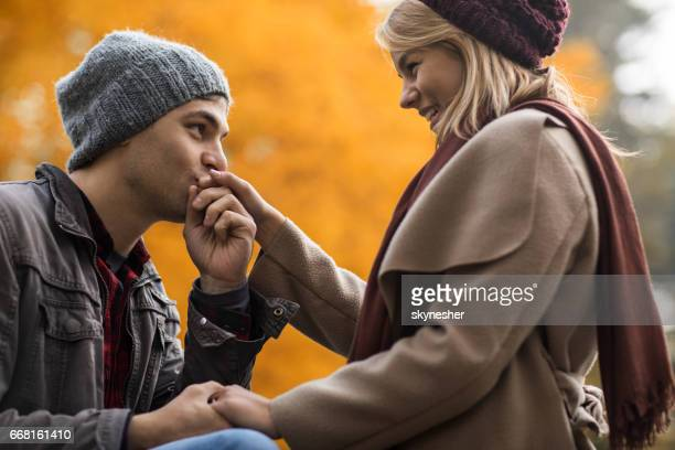 Young man kissing girlfriend's hand in in nature during autumn.