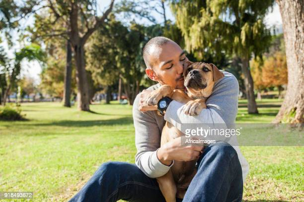 Young man kissing his puppy while sitting on the grass at the park.