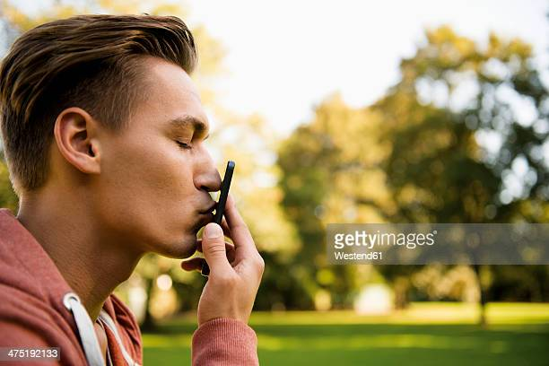 young man kissing his smart phone, close-up - hair love stock pictures, royalty-free photos & images