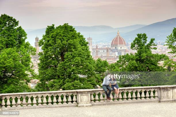 young man kissing woman, santa maria del fiore in background, florence, toscana, italy - florence italy foto e immagini stock