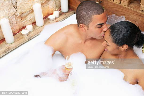 young man kissing young woman in a bathtub - couple and kiss and bathroom stock photos and pictures