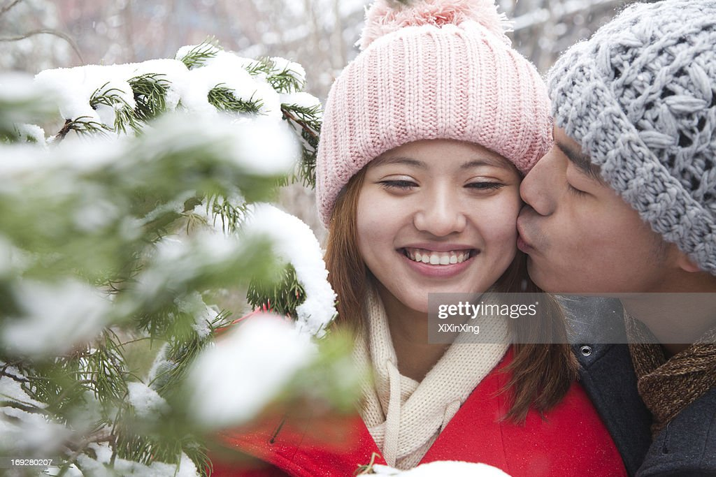 Young man kissing young woman in park in snow : Stock Photo