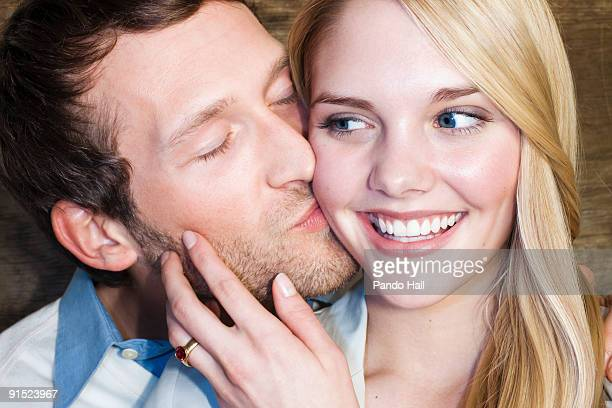 Young man kissing young woman on cheek, smiling