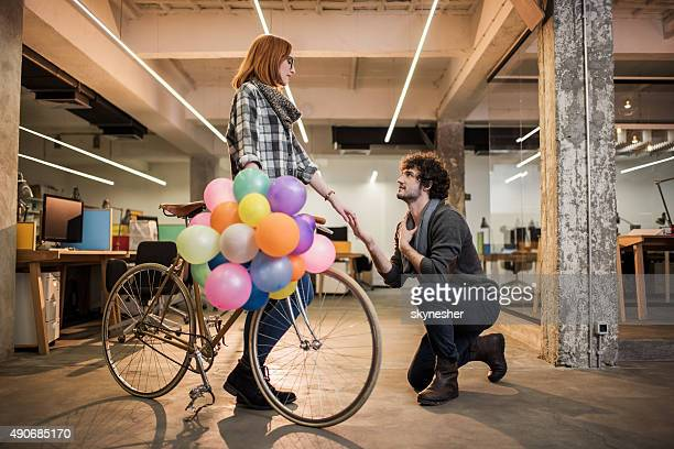Young man kneeling and proposing his girlfriend.