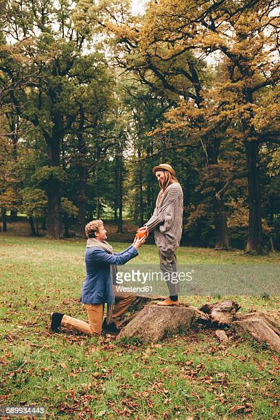 Young man kneeling down and proposing to his girlfriend in an autumnal park