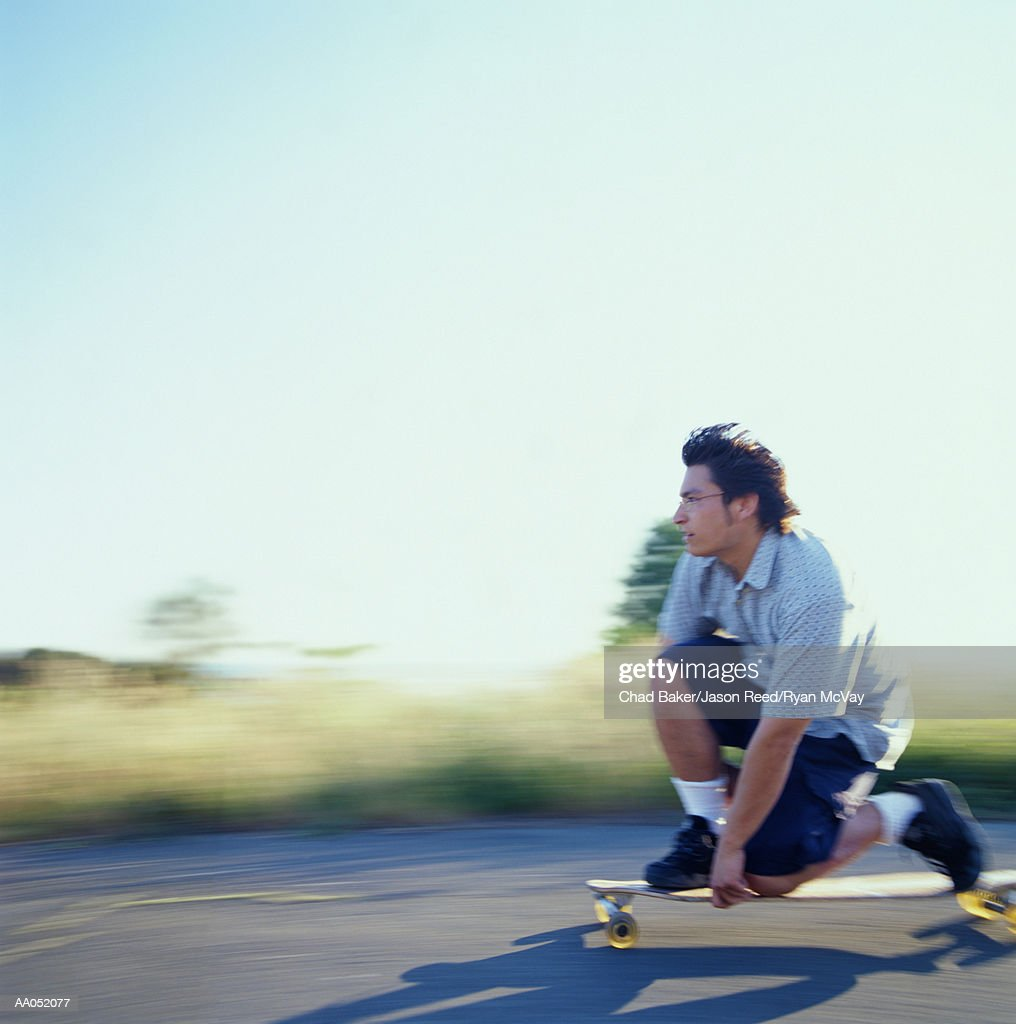 Young man kneeling down on longboard, side view (blurred motion) : Stockfoto