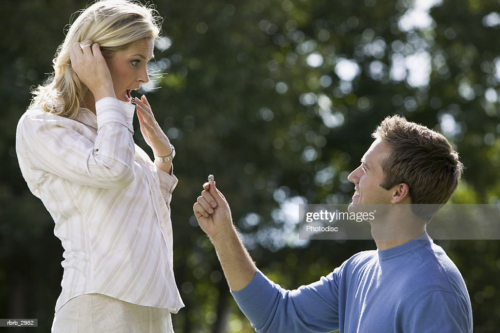Young man kneeling down with a ring proposing to a young woman : Foto de stock