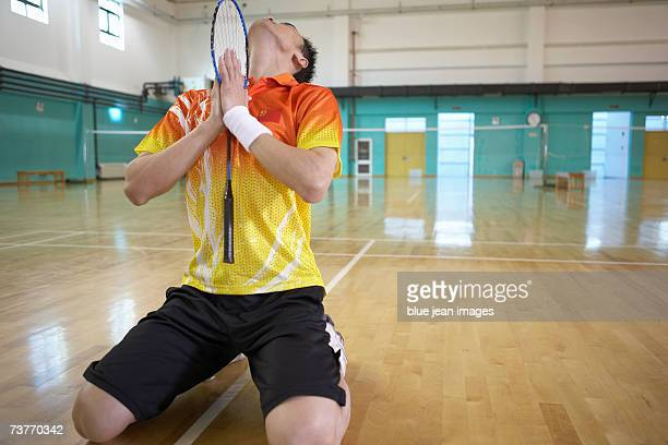 Young man kneels and holds his badminton racket as if praying.