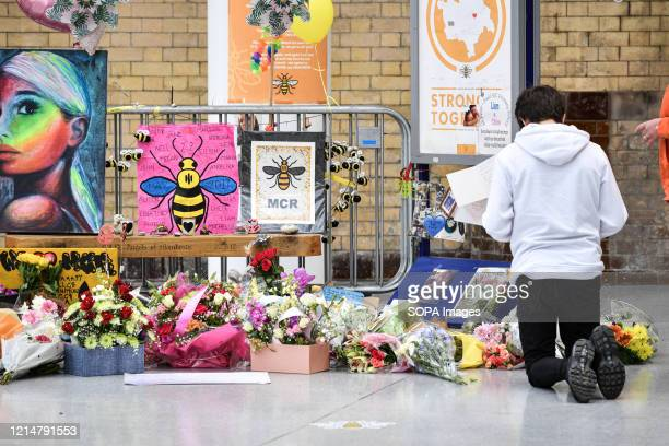 A young man kneels in front of the floral memorial at Victoria station during the commemoration People gather at Victoria station to mark the third...