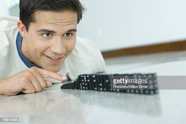 Young man knocking over line of dominos