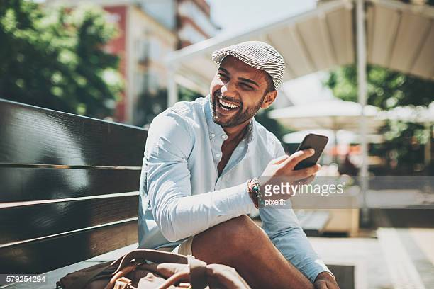 Young man laughing at a text message