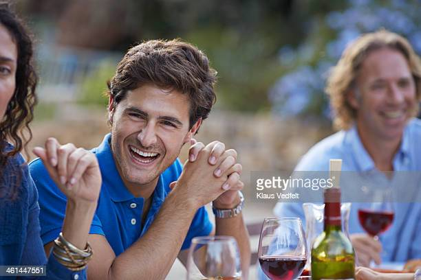 young man laughing at dinner party - klaus vedfelt mallorca stock pictures, royalty-free photos & images