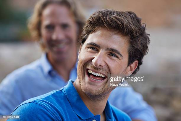 Young man laughing at family garden party