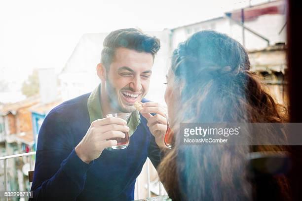Junger Mann lacht während Seite des Freundinnen genießen Tee
