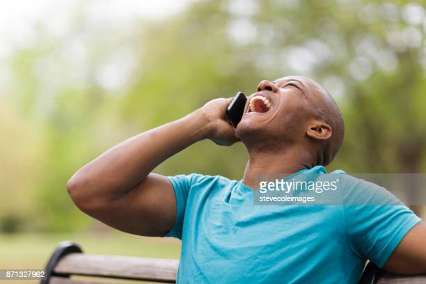 Young man laughing while on mobile phone.