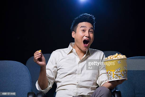 Young man laughing while watching movie