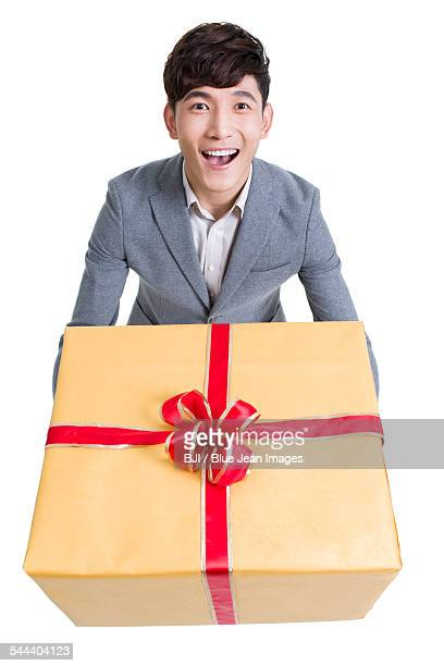 Young man laughing with a large gift