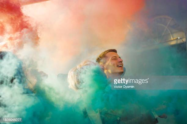 young man laughs cheerfully in the colorful smoke - ウクライナ オデッサ市 ストックフォトと画像