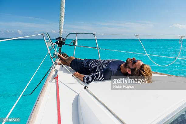 young man laying down at the bow of sailboat - down blouse stock pictures, royalty-free photos & images
