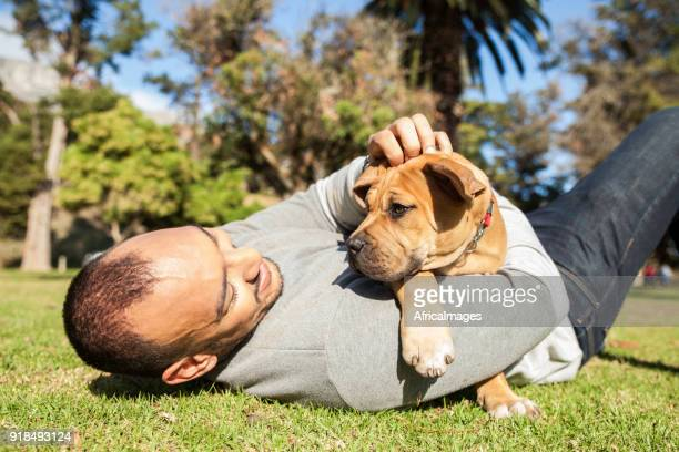 Young man laying on the grass holding his puppy.