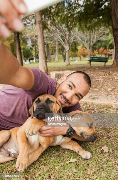 Young man laying on the grass taking selfies of him and his puppies.